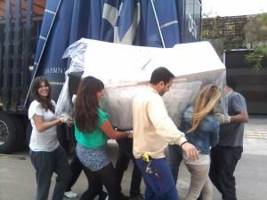 Alumnos transportan los materiales recibidos.