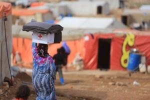 Una mujer siria carga con material proporcionado por Cruz Roja. / Foto: prensacruzroja.es