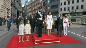 Los Reyes junto a sus hijas y el presidente del Gobierno escuchando el Himno de España.