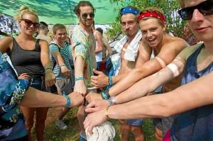 Chicos y chicas enseñan las pulseras del festival