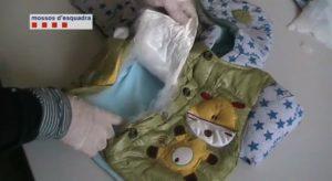 Mossos D'Escuadra desmantelando un cogín infantil lleno de droga.