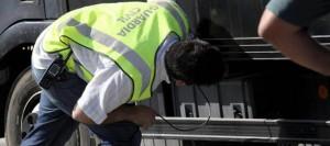 Agente en busca de algún inmigrante escondido en los bajos de un camión