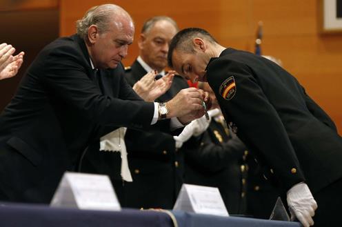 El ministro coloca su condecoración a uno de los agentes homenajeados.