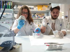 Los técnicos de laboratorio Irene López y Jorge Rivera cogiendo volúmenes concretos de soluciones líquidas.