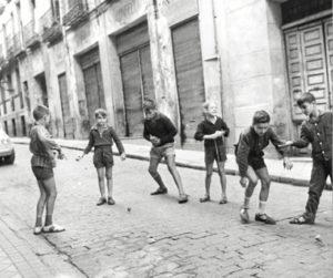 Niño tirando la peonza en las calles de la capital.