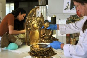 Una investigadora trabaja en la restauración de un buda en el IPCE. / Foto: Comunicación CSIC